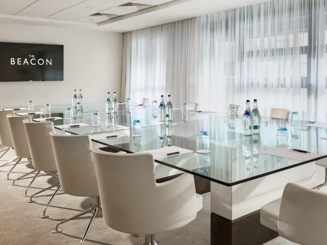 meeting room with glass table and white chairs